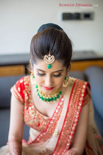 Contrast jewellery in emerald green with red lehenga