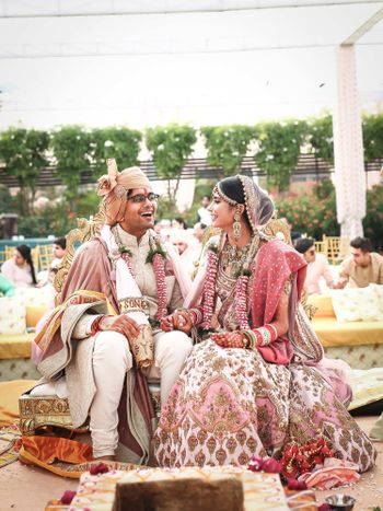 A bride and groom in color-coordinated pink outfits at their wedding