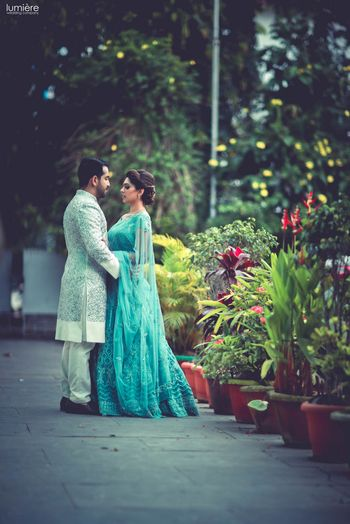 Photo of Outdoor couple shoot with bride in teal lehenga