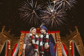 A couple poses infront of fireworks on their wedding day