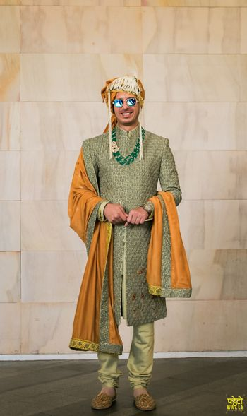 Groom in an olive green sherwani with a mustard dupatta