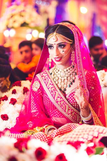 Bride dressed in a red lehenga posing while making an entry.