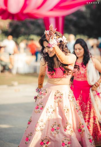Photo of A bride in a pink lehenga and floral jewellery for her mehndi ceremony