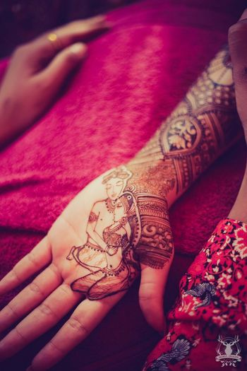 Intricate mehendi design with bride and groom