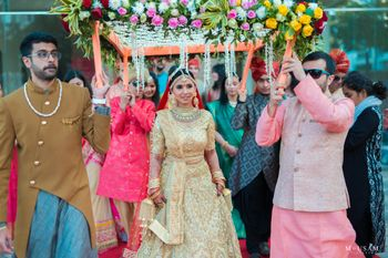 bride in gold lehenga entering under phoolon ka chadar
