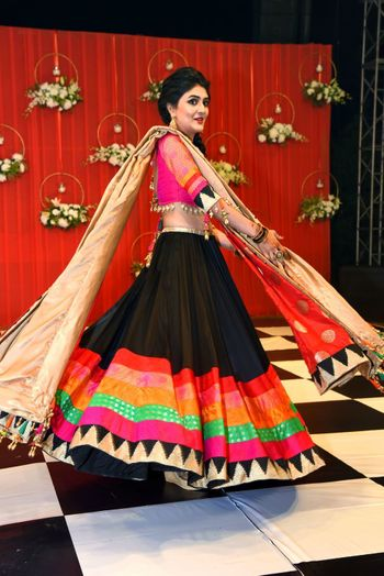 Bride twirling in quirky colourful lehenga