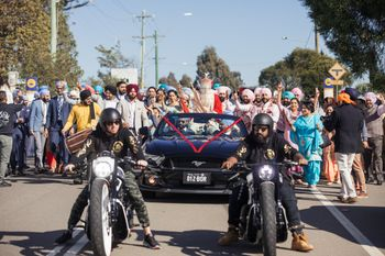 Photo of A groom enters on a vintage car with a bike entourage