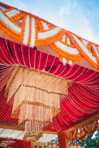 Photo of orange red and white mandap