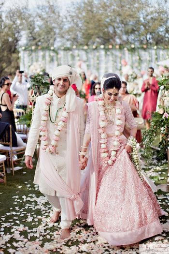 Photo of Bride and groom in light pink with matching jaimalas