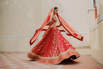 Photo of Red and gold sabyasachi bridal lehenga twirling