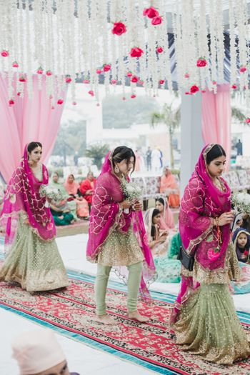 Bridesmaids in coordinated outfits of pink and green