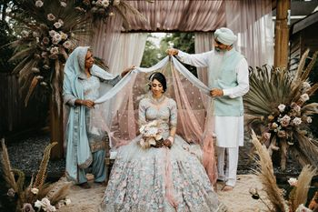 Bride getting ready with her parents draping the dupatta over her