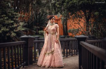 Photo of A bride in a soft pink lehenga and double dupatta