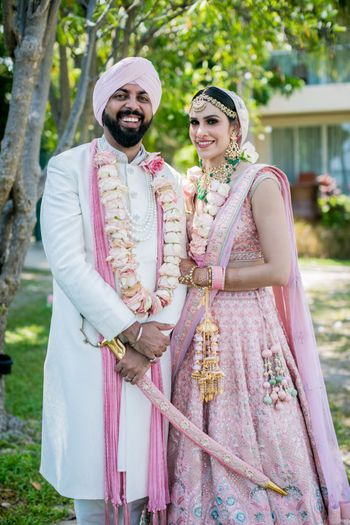 Photo of Bride and groom twinning in pastel pink outfits.