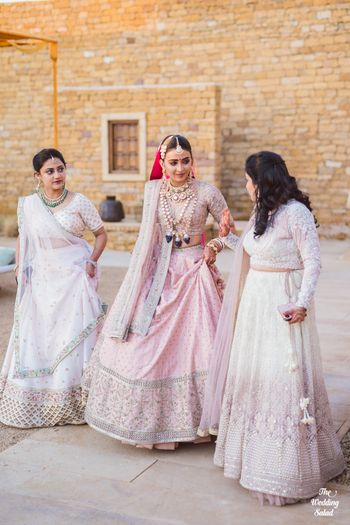 bride in a light pink lehenga with her bridesmaids matching in white