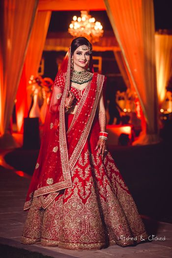 Red bridal lehenga with green jewellery
