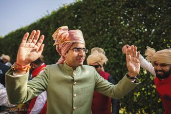 Groom in sage green sherwani and peach pink safa
