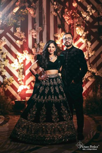Photo of matching bride and groom in black on their sangeet