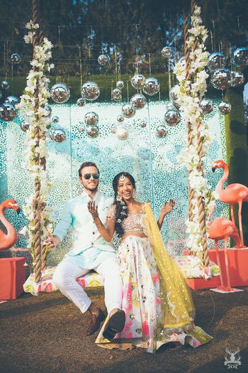 Photo of Mehendi couple portrait with hanging glass balls and swing