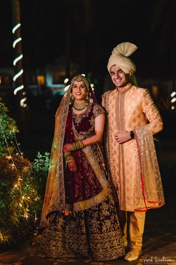 Contrasting bride and groom with maroon lehenga and peach sherwani