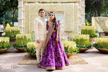 A couple poses in front of a mogra flower decoration for their sangeet ceremony