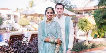 A bride and groom in coodinated blue outfits for their wedding