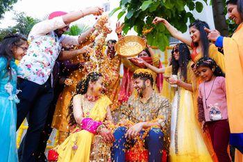 Bride & groom showered with flowers on Haldi