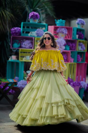 Photo of Twirling bride in mustard off shoulder blouse with frill skirt for mehendi