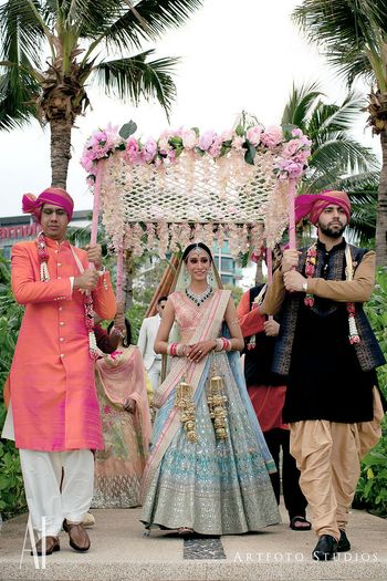 Photo of Offbeat bride in light pink and blue gota Patti lehenga entering