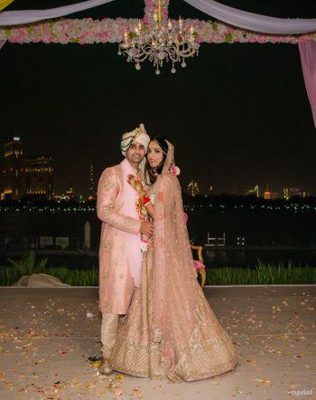 Photo of Light pink bride and groom sherwani