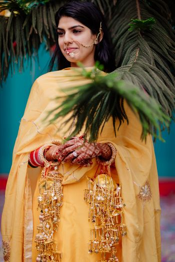 A bride in a simple yellow outfit her haldi