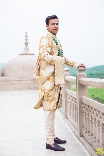 Photo of Groom in gold and white sherwani with green necklace