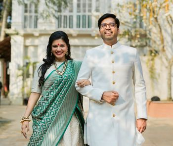 Photo of Matching bride and groom in white with bride holding green banarasi dupatta