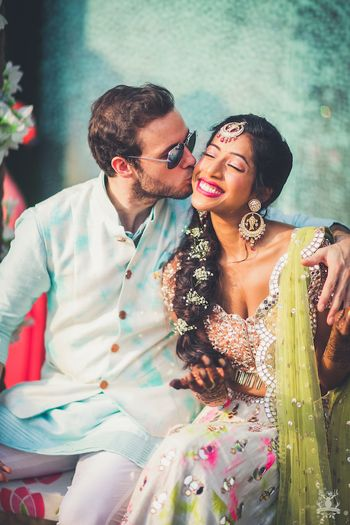 Photo of Mehendi couple portrait groom kissing bride shot