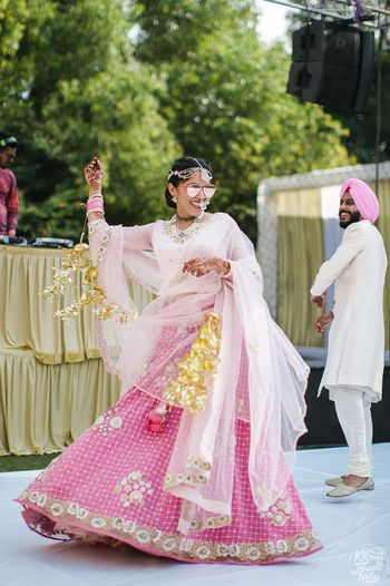 Photo of Bride dancing in light pink minimal bridal lehenga