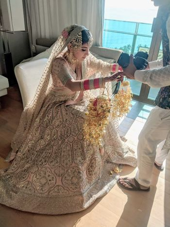 bride with her bridal kaleere in a pink and gold lehenga