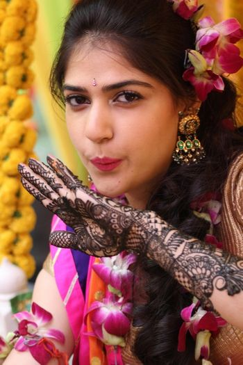 briaded hairstyle with floral porchid in hair mehendi hairstyle