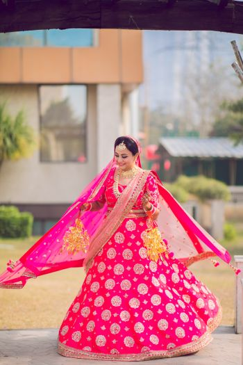 Photo of Bride twirling in a pink lehenga on her wedding day.