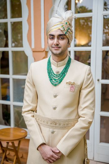 Groom wearing an off-white sherwani with a layered necklace.