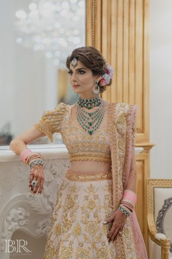 bride in unique lehenga by abu jani and green jewellery
