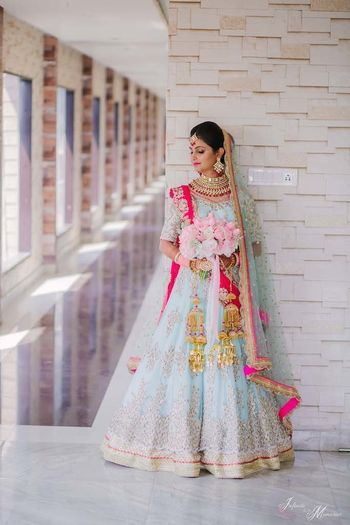A bride in powder blue lehenga holding a bouquet of roses
