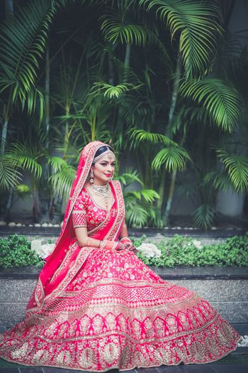 Photo of Red and gold Sabyasachi bridal lehenga with floral motifs