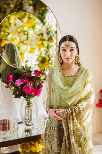 A to-be-bride in a green sharara for her roka ceremony
