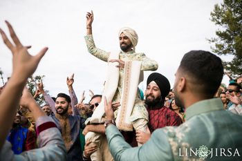 Photo of Groom entering on brothers shoulders
