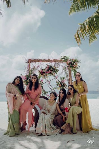 Photo of beach mehendi photobooth with bride and bridesmaids