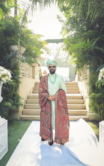 Happy groom dressed in mint green sherwani