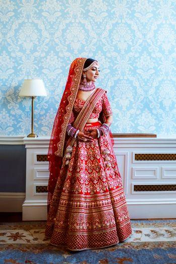 Bride wearing a red bridal lehenga.