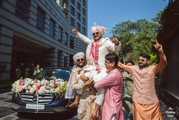 Photo of groom baraat entry idea on groomsmen shoulders