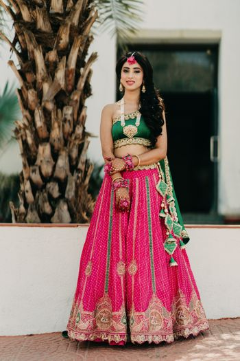 Bride wearing a green one-shoulder blouse with a pink lehenga.