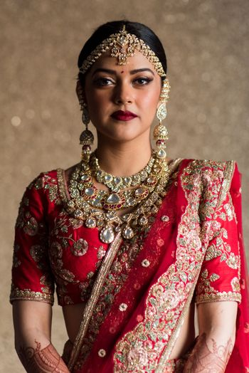 Modern bridal portrait in red and gold lehenga